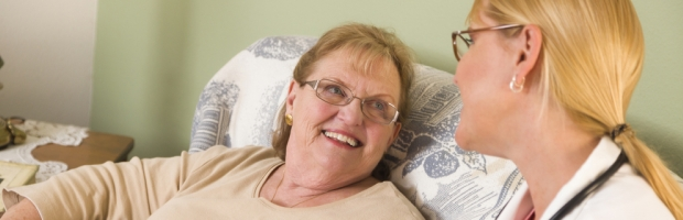 Happy Smiling Doctor or Nurse Talking to Senior Woman in Chair