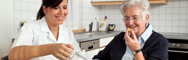 A geriatric nurse helps elderly woman at breakfast